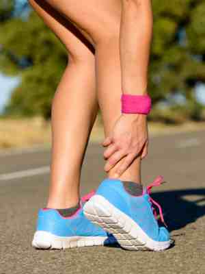 Woman with pain in her ankle walking on a road surface