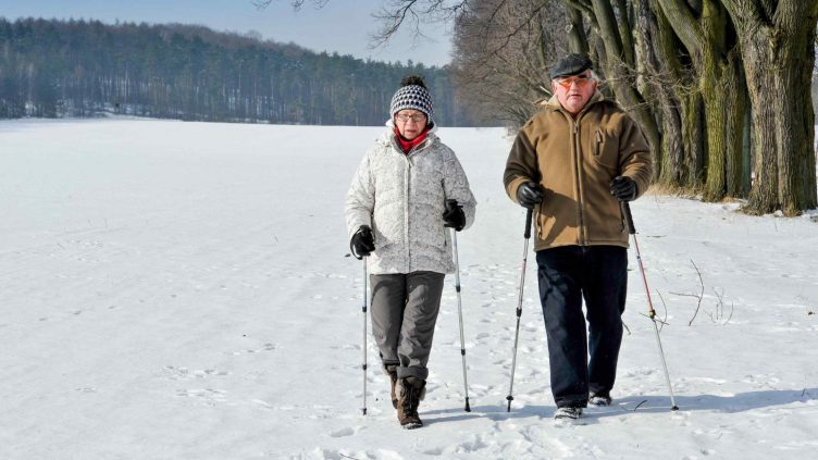 Couple walking nordic style in the winter snow